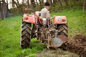 stock photo of plowed field  - Senior farmer using an old tractor to plow his land - JPG