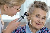 foto of otoscope  - Doctor performing ear exam with otoscope on a  senior patient - JPG