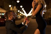 stock photo of propose  - A man in a suit proposing to his beautiful woman at night - JPG