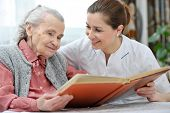 stock photo of granddaughters  - Senior woman and nurse looking together at album with old photographs - JPG