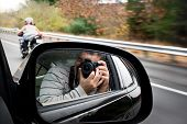 stock photo of crotch  - A paparazzi photographer takes a photo of a woman driving a motorcycle on the highway - JPG