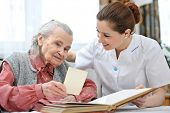 image of hospice  - Senior woman and nurse looking together at album with old photographs - JPG