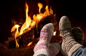 stock photo of hot couple  - Couple relaxing at the fireplace on winter evening - JPG