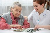 stock photo of geriatric  - Senior woman playing checkers with a nurse in a retirement home - JPG