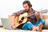 pic of fret  - Man on sofa playing the guitar with laptop at home - JPG