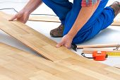 pic of carpenter  - carpenter worker installing laminate flooring in the room - JPG