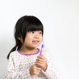 picture of pyjama  - Little Asian girl in pyjamas holding toothbrush - JPG