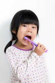 foto of pyjama  - Little Asian girl in pyjamas brushing teeth - JPG
