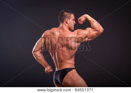 Athletic man showing muscles tense