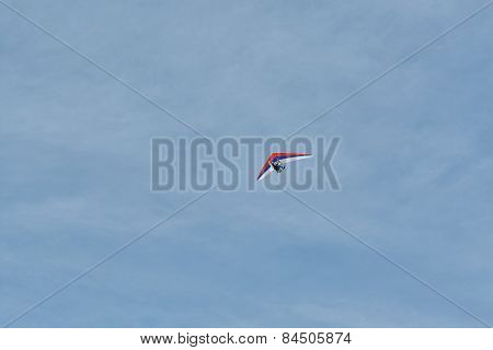 The Hang-glider Flying Against A Blue Sky With Clouds