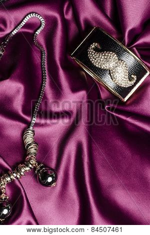Necklace With Black Beads And Bracelet  On Silk Background
