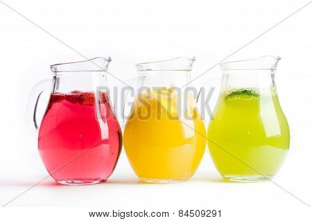 Three Pitchers With Red, Yellow, Green Fruit Juice On A White Background