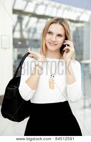 Young Female Walking In Fashionable Outfit Making Call On Mobile Phone