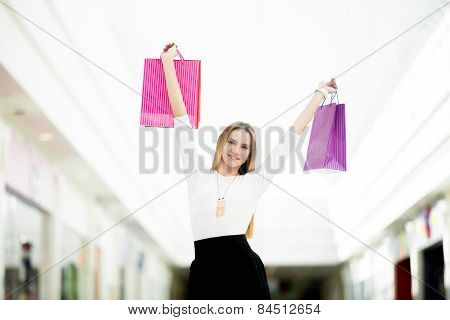 Smiling Young Woman Holding Up Shopping Bags With Joy