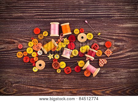 Collection Of Spools  Threads In Yellow-red Colors Arranged On A Grunge Wooden Box
