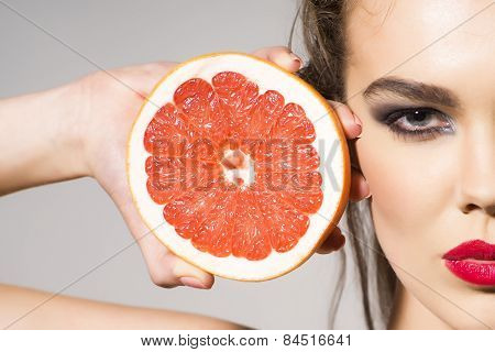 Preatty Girl Holding Grapefruit Cut In Half Next To The Head