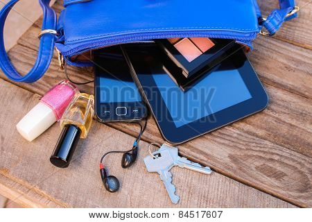Blue women's purse. Things from open lady handbag.