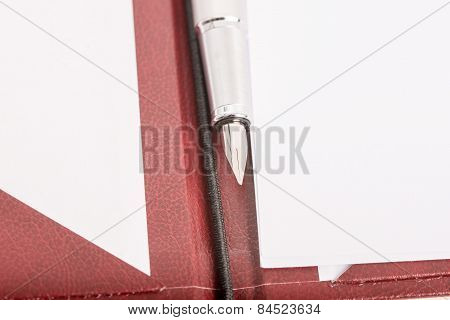 Ink Pen On An Open Leather Folder With Blank White Papers