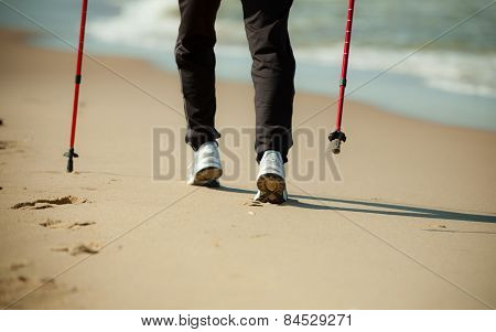 Nordic Walking. Female Legs Hiking On The Beach.