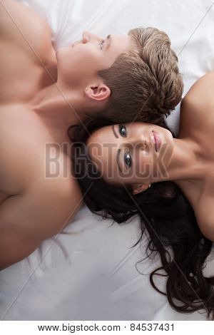 Lovers in bed. Top view of sexy brown-eyed woman