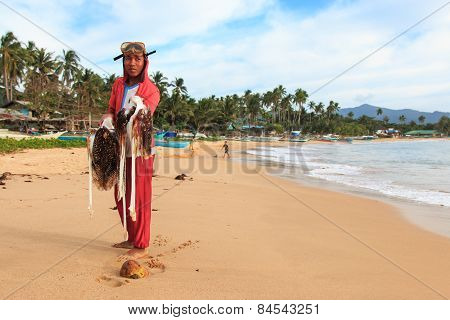 Nacpan, Philippines - 17 January 2015: Young Fisherman With His Catch On Nacpan Beach, Palawan In Th