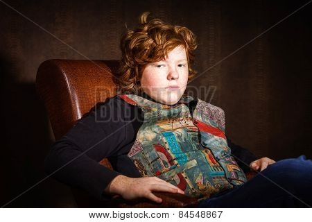 Red-haired Expressive Teenage Boy Sitting In Arm-chair