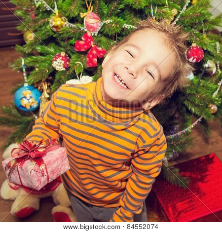 Christmas portrait of a happy child with a gift.