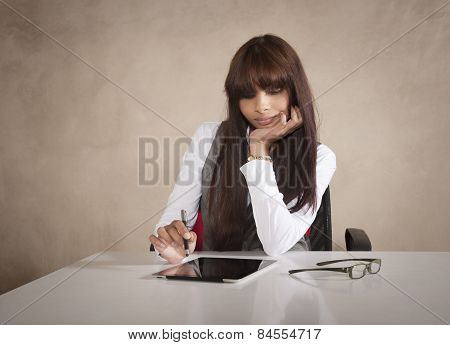 Young attractive Indian business woman working on digital tablet at desk
