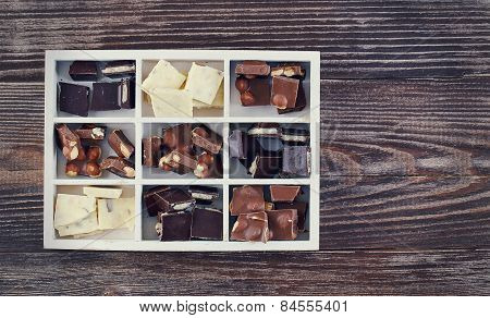 Wooden Box With Set Of Dark, White And Milk Chocolate On Wooden Table