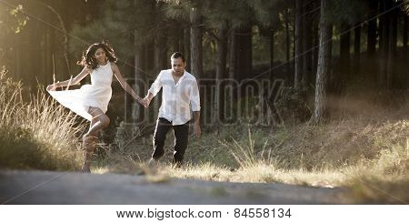 Young happy Indian couple skipping along dirt road