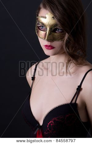 Portrait Of Beautiful Woman In Lingerie And Mask Over Grey