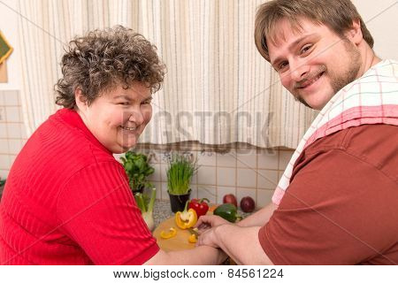 Mentally Disabled Woman And A Young Man Cooking Together