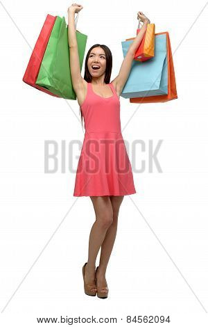 Asian young woman after shopping with hands up and bags
