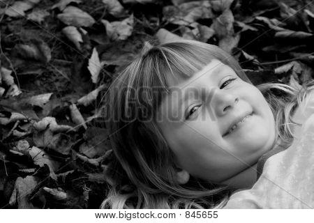 Chica en la pila de hoja