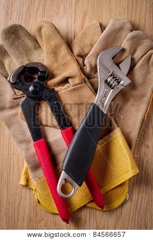 Adjustable Wrench And Nail Puller On Top Of The Protective Gloves