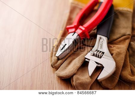 Adjustable Wrench And Pliers On Top Of The Protective Gloves