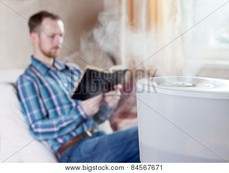 Man Reading Book On The Background Of Humidifier
