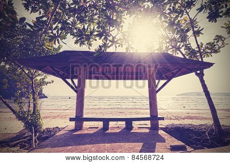 Retro Filtered Photo Of A Seaside Bench At Sunset.