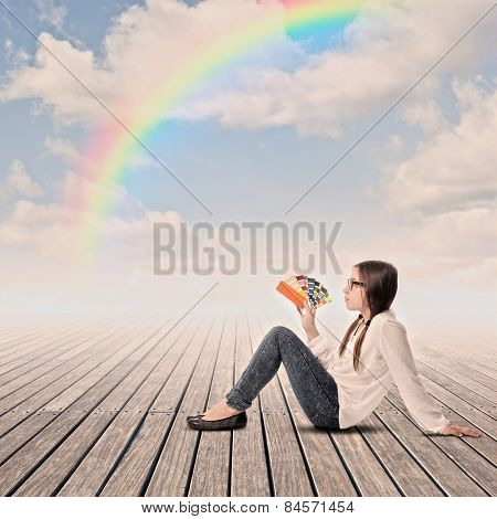 young girl holding a palette on a wharf with rainbow in the sky