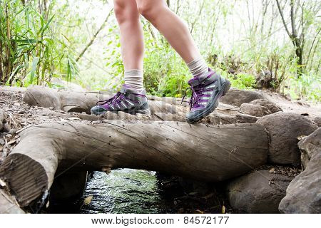Woman hiking on top of a stream