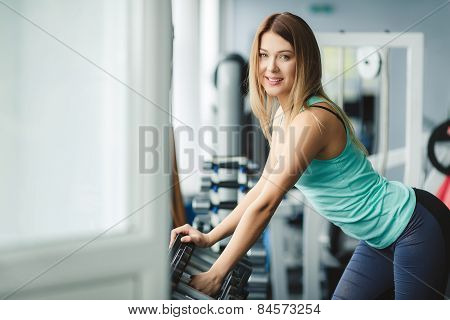 Beautiful girl fitness trainer chooses dumbbells for training.