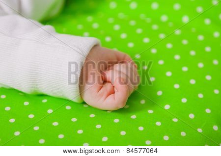 Hand of a little baby sleeping on a  cushion