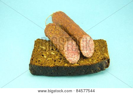 Brown  Bread And Sausage On Blue Background