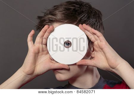 Teenage Boy Is Looking Through The Hole Of A White Disc, With Gray Background For Fast Isolating