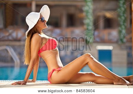 Beautiful Woman Enjoying By The Swimming Pool