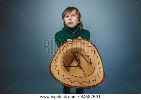 European-looking boy of ten years in glasses holding a hat,