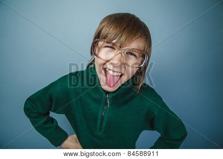 European-looking boy of ten years in glasses showing tongue on a