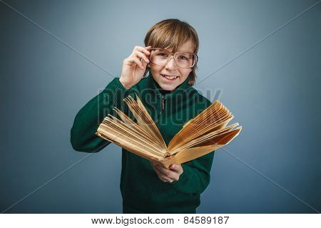 European -looking boy of  ten years in  glasses reading  a book
