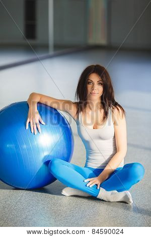Yoga woman sitting and resting on a fitness ball