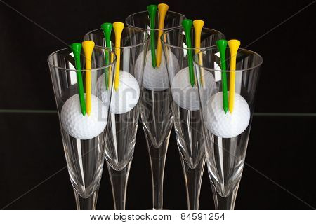 Five Glasses Of Champagne And White Golf Balls